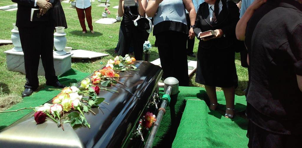 burial of a coffin with flowers or cremation
